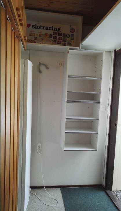 Toinen kuva tyhjennetystä varastosta, jossa hyllyt ja kaapit ovat vielä paikoillaan.