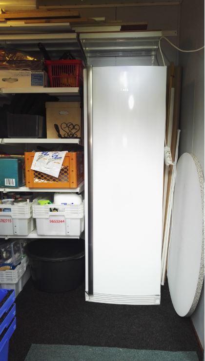 Kuvassa varastossa oleva pakastin ja pieni osan pitkän seinän hyllyistä.